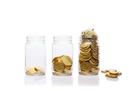Glass jars with growing amount of gold coins. Savings and wealth management concept Horizontal