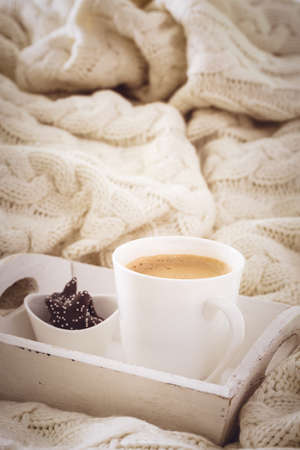 Hot beverage mug with chocolate cookies in a white wool blanket. Hot drink, cozy home and cold season concept. Vertical, toned image