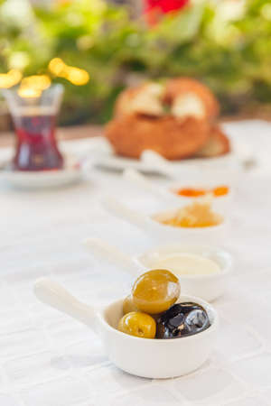 Turkish tea, Honey, Jam,  Olives. Authentic turkish breakfast. Local cuisine concept. Soft focus. Vertical