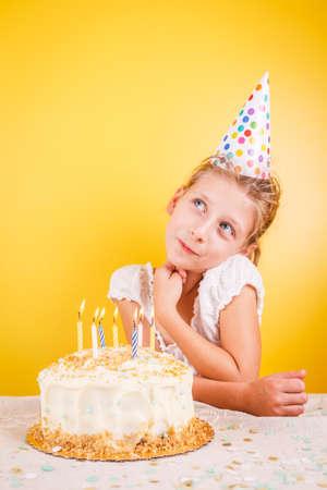 Girl making a wish by birthday cake. Birthday party celebration concept. Vertical Standard-Bild - 120552891