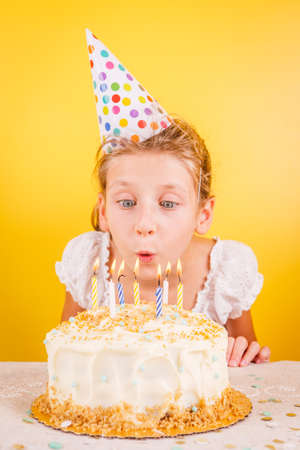 Girl blowing out candles on birthday cake. Birthday party celebration concept. Vertical Standard-Bild - 120552894