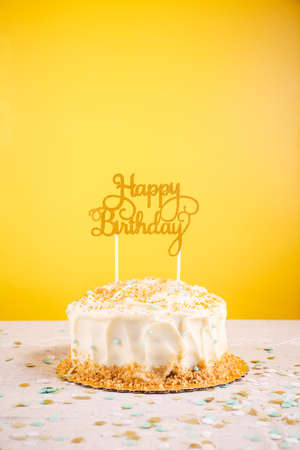 Birthday cake with golden topper. Birthday party celebration concept. Vertical, bold yellow background