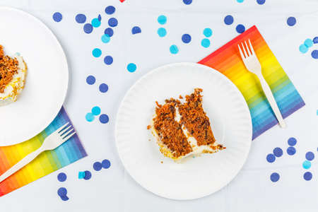 Flat lay with birthday cake pieces on white paper plates. Birthday party celebration concept. Horizontal, close up