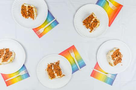 Flat lay with birthday cake pieces on white paper plates. Birthday party celebration concept. Horizontal Stock Photo
