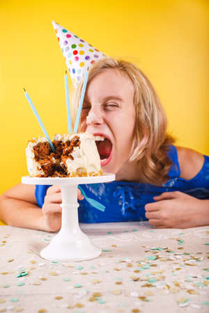 Teenage girl eating  birthday cake with her hands. One person party. Concept of birthday party, messthetics and misconduct. Vertical Stock Photo