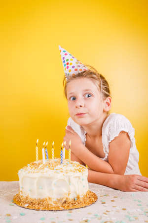 Girl making a wish by birthday cake. Birthday party celebration concept. Vertical