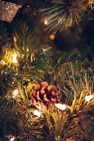 Seasonal background with pine cone on the Christmas tree. Celebration concept. Soft focus. Vertical
