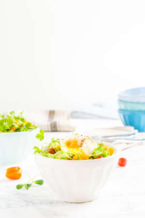 Mixed baby greens and cherry tomatoes salad with avocado and poached egg in bowl. Superfood snack concept. Vertical Stock Photo