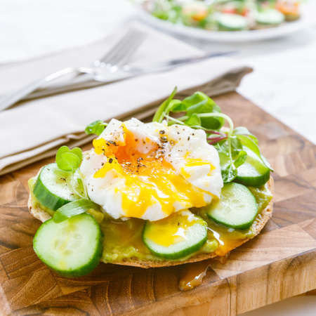 Raw healthy burger with avocado dressing, cucumbers, poached egg and multigrain bread. Superfood snack concept. Square