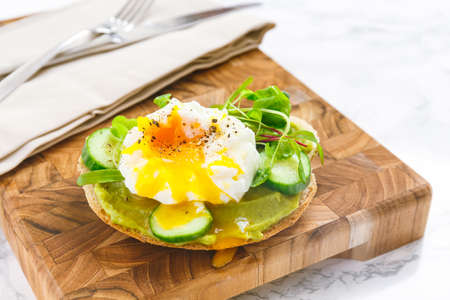 Raw healthy burger with avocado dressing, cucumbers, poached egg and multigrain bread. Superfood snack concept. Horizontal