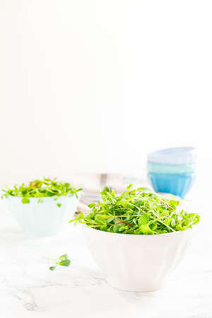 Mixed baby greens salad in bowl. Superfood snack concept. Vertical Stock Photo