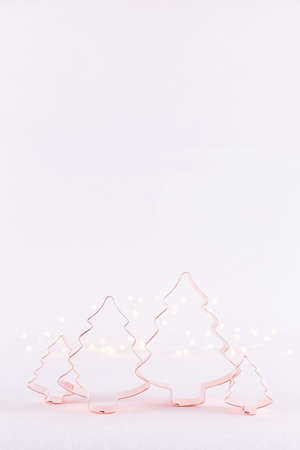 Family of Christmas Tree Copper cookie cutters on white sparkling background with bokeh lights. Holiday Christmas and New Year background. Vertical