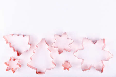 Flatlay with holiday tree and snowflake copper cookie cutters on white sparkling background. Holiday, Christmas and New Year concept. Cozy homey details. Flat lay, top view background. Horizontal