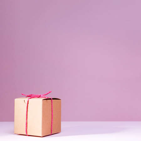Craft cardboard gift box on the solid pink background. Holiday and gift concept. Square