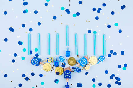 Blue confetti  background with menora made of dreidels and chocolate coins. Hanukkah and judaic holiday concept. Horizontal Stockfoto