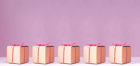 Craft cardboard gift boxes on the solid pink background. Holiday and gift concept. Pop art slyle. Horizontal, wide screen banner format
