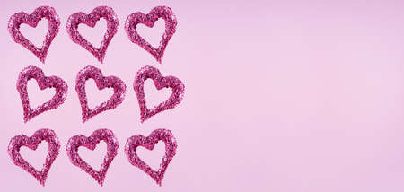 Glitter hearts on pink background.  Valentines day and love concept. Horizontal wide screen banner format