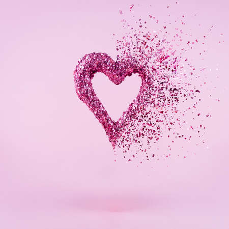 Glitter heart dissolving into pieces on pink background.  Valentines day, broken heart and love emergence concept. Square Stock Photo