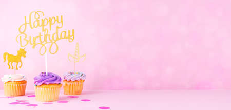 Creative pastel fantasy holiday card with cupcake, happy birthday topper and unicorn on bokeh backdrop. Baby shower, birthday, celebration concept. Horizontal, wide screen banner format