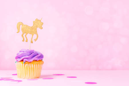 Creative pastel fantasy holiday card with cupcake, confetti and unicorn on bokeh backdrop. Baby shower, birthday, celebration concept. Horizontal