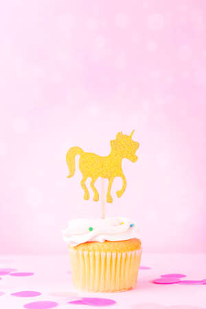 Creative pastel fantasy holiday card with cupcake, confetti and unicorn on bokeh backdrop. Baby shower, birthday, celebration concept. Vertical