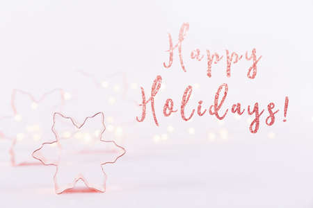 Snowflake Copper cookie cutters on white sparkling background with bokeh lights. Holiday Christmas and New Year card background. Horizontal. Holiday wording