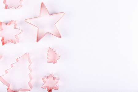 Flatlay with snowflakes, star and holiday tree copper cookie cutters on white sparkling background. Holiday, Christmas and New Year concept. Flat lay, top view background. Horizontal, right side for text