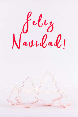 Family of Christmas Tree Copper cookie cutters on white sparkling background with bokeh lights. Holiday Christmas and New Year card background. Vertical. Holiday wording in Spanish