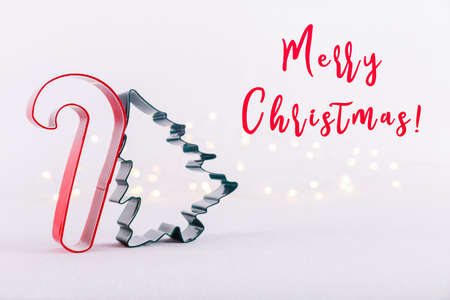 Candy cane and Christmas tree cookie cutters on white sparkling background with bokeh lights. Holiday Christmas card background. Horizontal. Holiday wording