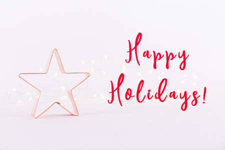 Star Copper cookie cutter on white sparkling background with bokeh lights. Holiday Christmas and New Year card background. Horizontal. Holiday wording Stock Photo