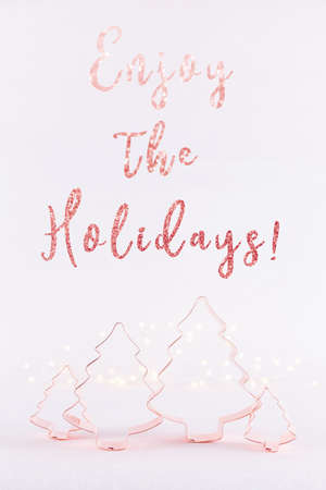 Family of Christmas Tree Copper cookie cutters on white sparkling background with bokeh lights. Holiday Christmas and New Year card background. Vertical. Holiday wording Stock Photo