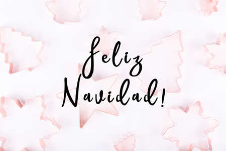 Flatlay with selection of holiday copper cookie cutters on white sparkling background. Holiday, Christmas card concept. Cozy homey details. Flat lay, top view background. Horizontal. Holiday wording in Spanish