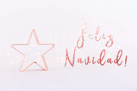 Star Copper cookie cutter on white sparkling background with bokeh lights. Holiday Christmas card background. Horizontal. Holiday wording in Spanish