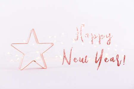 Star Copper cookie cutter on white sparkling background with bokeh lights. Holiday and New Year card background. Horizontal. Holiday wording