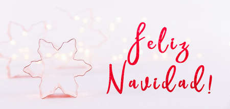 Snowflake Copper cookie cutters on white sparkling background with bokeh lights. Holiday Christmas and New Year card background. Horizontal. Holiday wording in Spanish, wide screen banner format