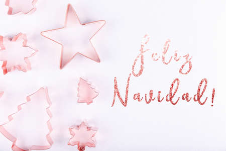 Flatlay with snowflakes, star and holiday tree copper cookie cutters on white sparkling background. Holiday, Christmas card concept. Cozy homey details. Flat lay, top view background. Horizontal. Holiday wording in Spanish