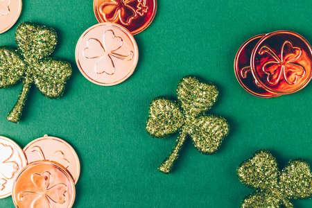 Glitter shamrocks and golden coins on green paper background. St Patricks day symbol. Irish National holiday concept. Horizontal Stock Photo
