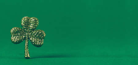 Glitter shamrock on green paper background. St Patricks day symbol. Irish National holiday concept. Horizontal, wide screen banner format