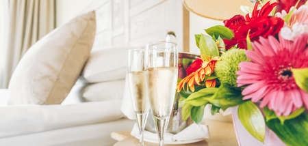 Two glasses of champagne in the upscale hotel room. Dating, romance, honeymoon, valentine, getaway concepts. Horizontal, banner wide screen format. Light warm toning