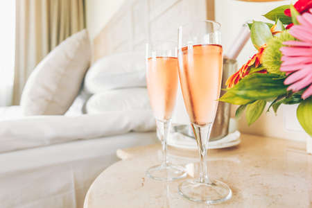 Two glasses of rose champagne in the upscale hotel room. Dating, romance, honeymoon, valentine, getaway concepts. Horizontal. Light warm toning