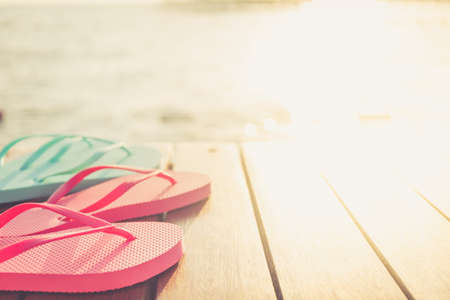 Flip flops at the wooden pier during sunset. Luxury vacation resort. Holiday getaway concept. Horizontal, warm toning