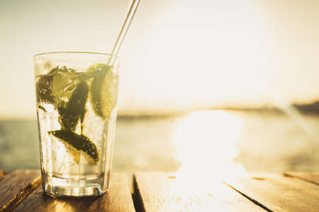 Cocktail at the wooden pier during sunset. Luxury vacation resort. Holiday getaway concept. Horizontal, warm toning