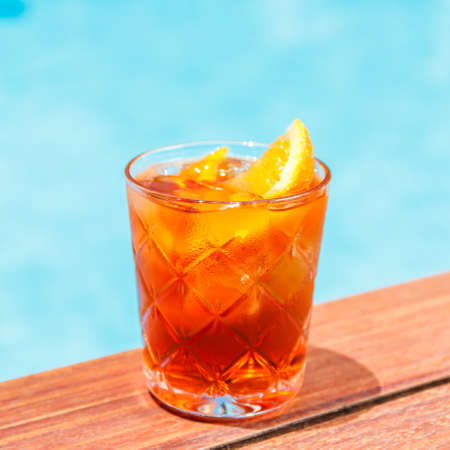 Negroni cocktail  near a pool at the resort bar or suite patio. Luxury resort, vacation, room service concept. Square
