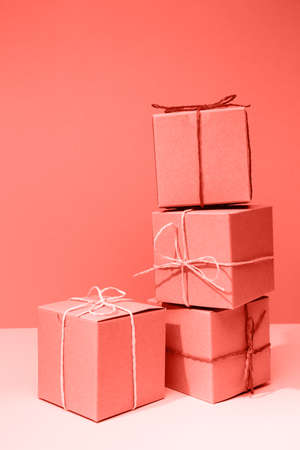 Craft cardboard boxes on the solid pink background. Holiday and gift concept. Vertical. Living coral theme - color of the year 2019