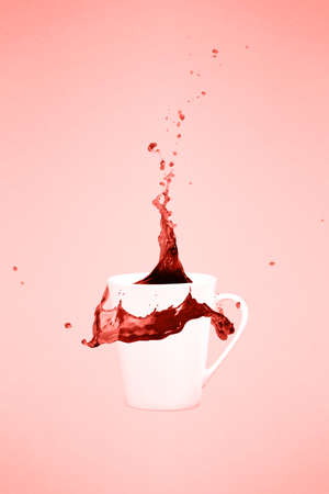 Two levitating coffee mugs with splashes. Coffee concept. Minimal art trend. Solid background. Vertical. Living coral theme - color of the year 2019