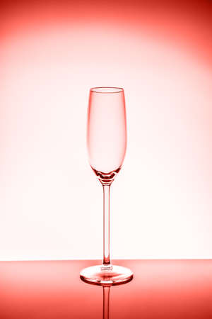 Champagne glass on the light background.. Fine cristal glassware concept. Vertical. Living coral theme - color of the year 2019 Banco de Imagens