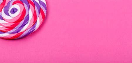 Big lollipop on solid pink background. Horizontal, banner format