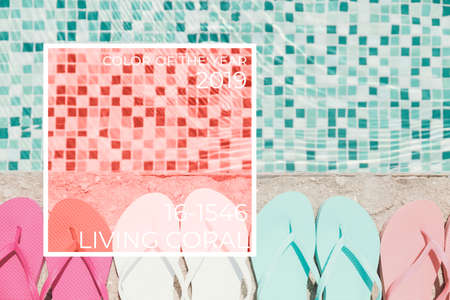 Flip flops at the pool border Horizontal. Living coral theme - color of the year 2019