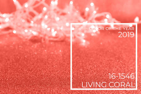 Holiday golden background with lights and bokeh. Christmas and New Year party concept. Stylish trendy holiday season. Horizontal. Living coral theme - color of the year 2019