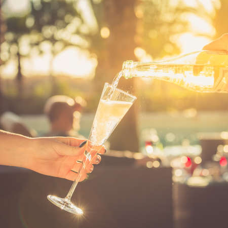 Waiter is pourring sparkling wine into a woman glass at the outdoor party.  Celebration concept. Event, party, wedding background. Toned image. Square Standard-Bild